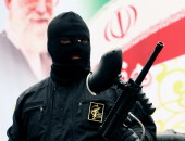 epa03014668 A Member of Iranian paramilitary Basij (volunteer) forces stands in front of a poster of Iranian supreme leader Ayatollah Khamenei during a parade in front the former US embassy in Tehran, Iran, 25 November 2011. Commander of Iran's Basij (volunteer) force Brigadier General Mohammad Reza Naqdi said that the volunteer forces are ready to respond any treats by Israel. He added that Basij fully prepared to defend Iran against enemies' treats.  EPA/ABEDIN TAHERKENAREH
